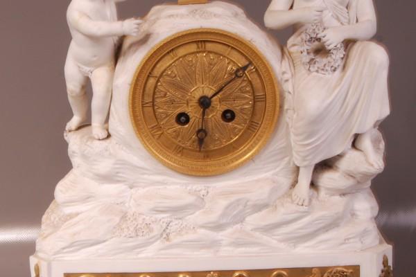 Pendule en biscuit et bronze doré  Epoque XIX° siècle